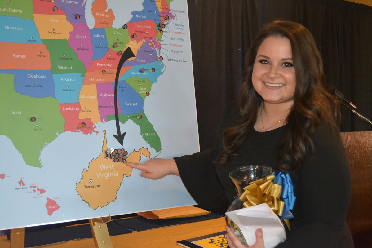 A young woman points to a map of West Virginia super-imposed outside a map of the U.S.